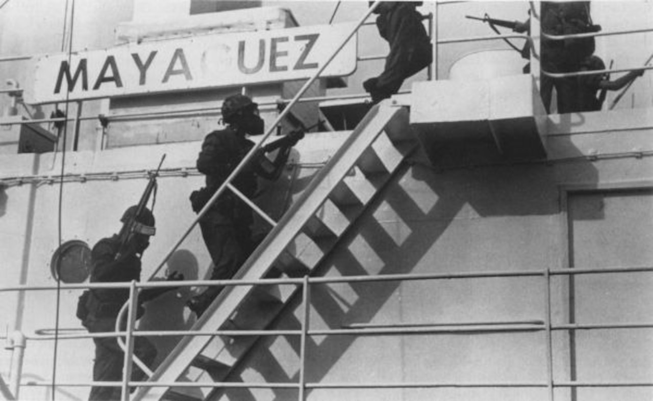 Marines climb stairs on a ship.