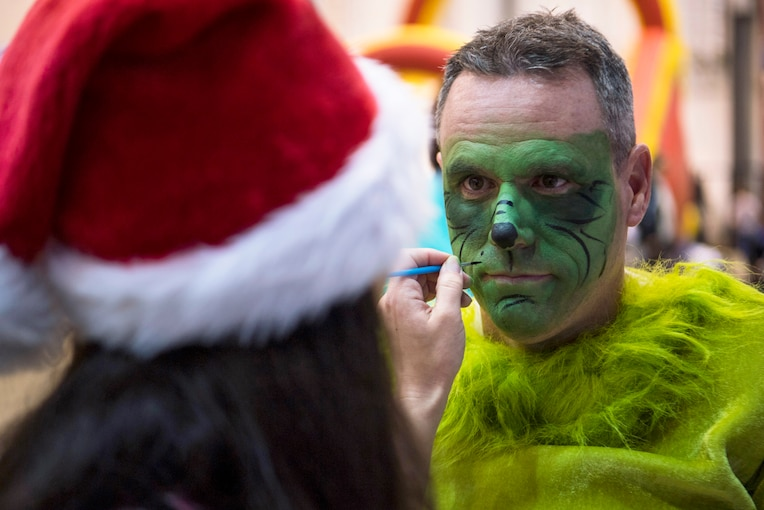 An airman in a green costume has his face painted green by someone in a Santa cap.