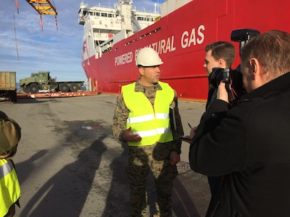 U.S. Marine Col. John Sullivan, 2d Marine Expeditionary Brigade chief of staff, is interviewed by Norweigan media as equipment that will be used during Trident Juncture 18 is offloaded at Trondheim Port, Norway, on Oct. 11, 2018. Trident Juncture 18 enhances the U.S. and NATO Allies' abilities to work together collectively to conduct military operations under challenging conditions. (U.S. Marine Corps photo by Maj. Jordan Cochran)