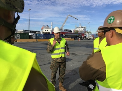 U.S. Marine Col. John Sullivan, 2d Marine Expeditionary Brigade chief of staff, speaks to U.S. Marines and Sailors, Norwegian Soldiers, and civilians as they work together to offload equipment that will be used during Trident Juncture 18 at Trondheim Port, Norway, on Oct. 11, 2018. Trident Juncture 18 enhances the U.S. and NATO Allies' abilities to work together collectively to conduct military operations under challenging conditions. (U.S. Marine Corps photo by Maj. Jordan Cochran)