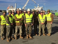 U.S. Marine Col. John Sullivan, 2d Marine Expeditionary Brigade chief of staff, stands with U.S. Marines and Sailors who worked together to offload equipment that will be used during Trident Juncture 18 at Trondheim Port, Norway, on Oct. 11, 2018. Trident Juncture 18 enhances the U.S. and NATO Allies' abilities to work together collectively to conduct military operations under challenging conditions. (U.S. Marine Corps photo by Maj. Jordan Cochran)