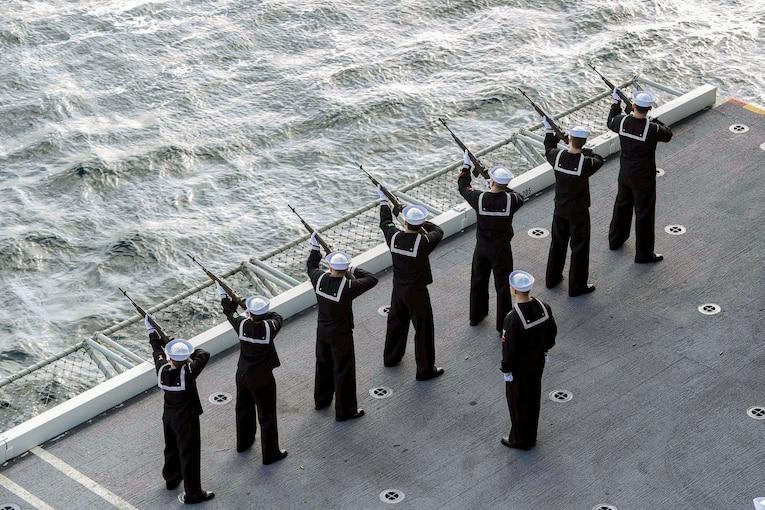 Sailors line up and fire rifles into the open sea.