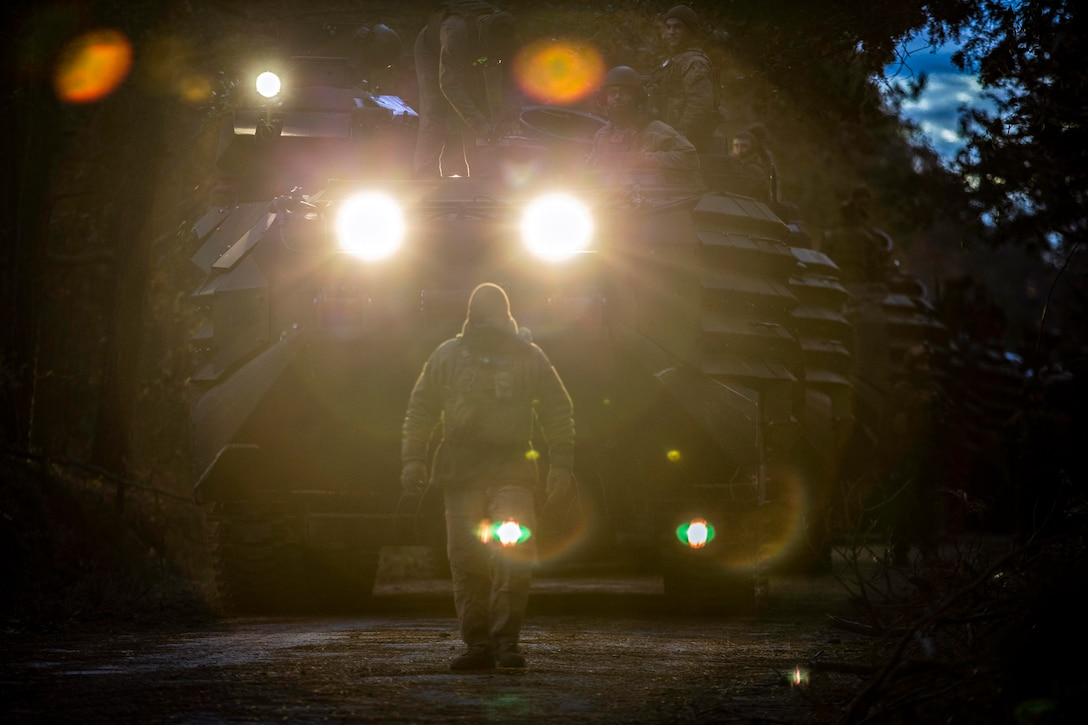 A Marine stands at attention before a large vehicle.