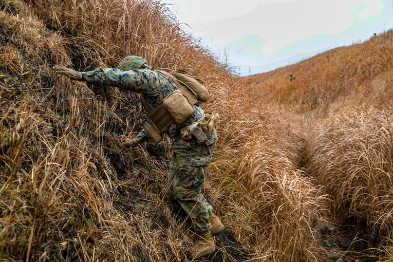 A Marine climbs a tall hill covered in grass.