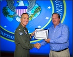 Photo of a male in a blue shirt and khaki pants receiving a certificate from another man in a Navy flight suit