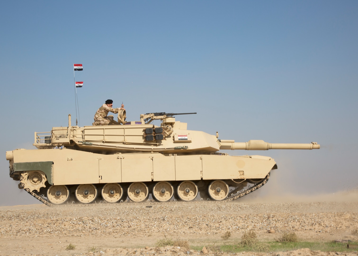 Iraqi soldier watches exercise from top of tank.