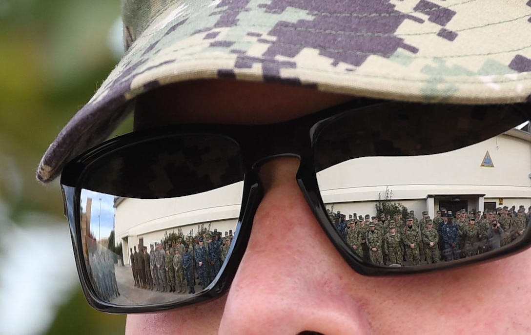 Keesler personnel attend the Center for Naval Aviation Technical Training Unit Keesler Pearl Harbor 77th Anniversary Remembrance Ceremony as seen through the sunglasses reflection of U.S. Navy Aviation Electronics Technician 1st Class Nathaniel Eakins, CNATTU Keesler instructor, at Keesler Air Force Base, Mississippi, Dec. 7, 2018. More than 100 Keesler personnel attended the event to honor those lost in the Dec. 7, 1941, Pearl Harbor attacks. (U.S. Air Force photo by Kemberly Groue)