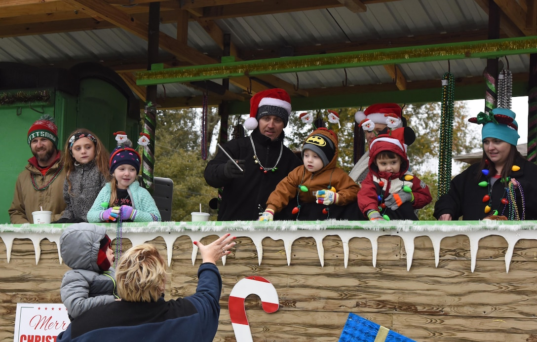 Passengers aboard decorated floats throw toys, candy and beads to families during the Ocean Springs Christmas Parade in Ocean Springs, Mississippi, Dec. 9, 2018. The Keesler Air Force Base Honor Guard and 81st Training Group Airmen participated in the event. (U.S. Air Force photo by Kemberly Groue)
