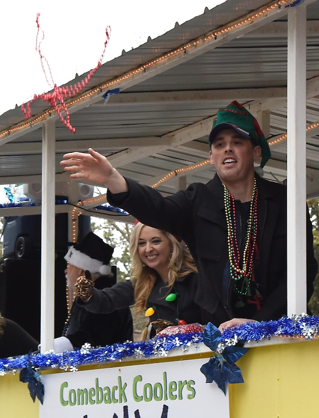 Shea Dobson, Ocean Springs Mayor, tosses beads into the crowd during the Ocean Springs Christmas Parade in Ocean Springs, Mississippi, Dec. 9, 2018. The Keesler Air Force Base Honor Guard and 81st Training Group Airmen participated in the event. (U.S. Air Force photo by Kemberly Groue)