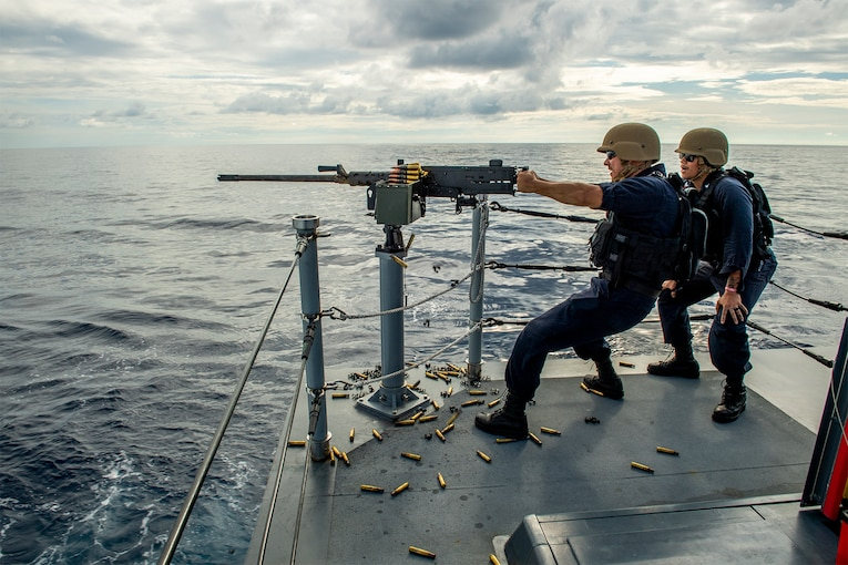 A sailor shoots a machine gun on a ship during a training exercise.