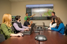 Jimmie Elliott, hydraulic engineer with the U.S. Army Corps of Engineers -Vicksburg District (MVK), addresses members of the Modeling, Mapping, and Consequences Production Center (MMC), at MVK, Nov. 27, 2018. In the background is the trafficability dashboard produced by the MMC. (USACE photo by Jared Eastman)