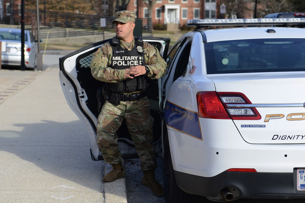 Specialist Rojas stands by his police car.
