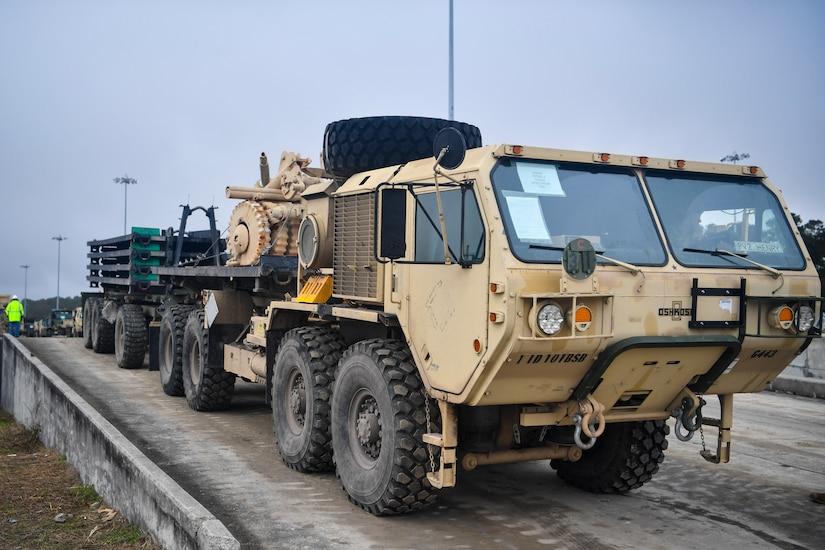 A Soldier from the 1st Infantry Division drives a military vehicle off a train during a vehicle offload Dec. 10, 2018, at Joint Base Charleston, S.C.