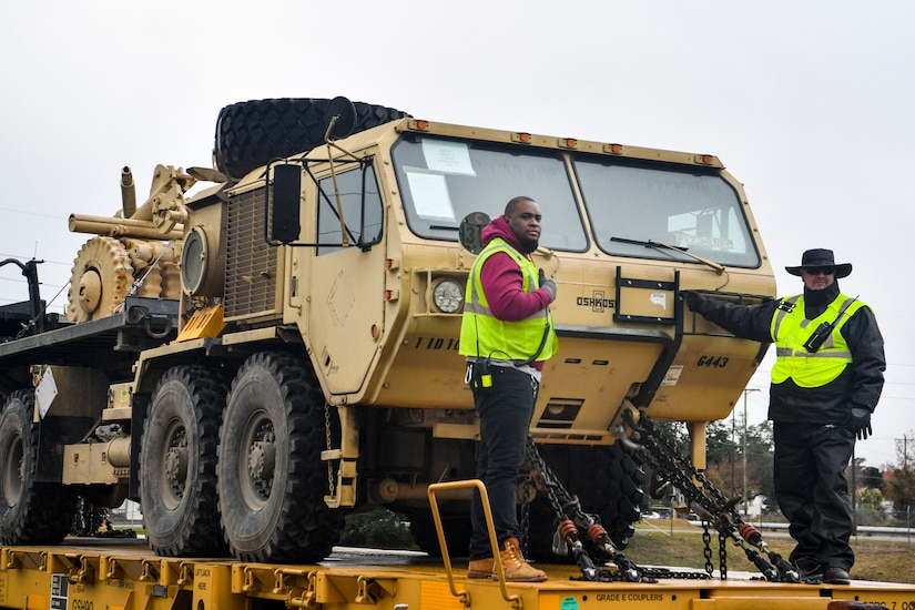 Members of the 841st Transportation Battalion ride with military vehicles on a rail flatcar Dec. 10, 2018, at Joint Base Charleston, S.C.