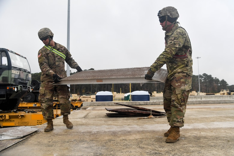 Soldiers from the 1st Infantry Division move a loading ramp Dec. 10, 2018, at Joint Base Charleston, S.C.