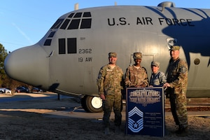 Four people in camouflage uniforms stand in front of a big gray plane with US Air Force on it.