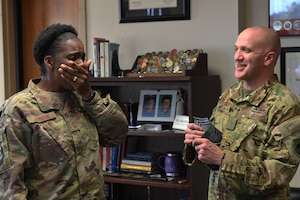 A black woman in camouflage uniform covers her mouth in surprise when a bald white man hands her new rank.