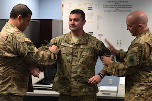 Two male Air Force Officers in camouflage put rank on another Air Force male.