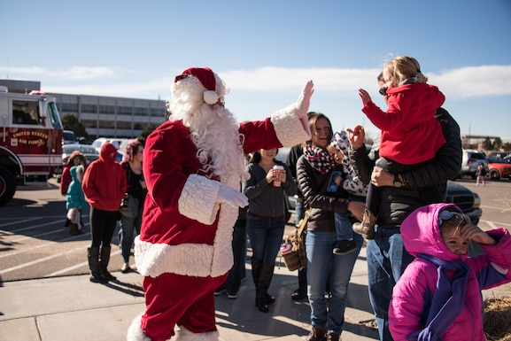 Santa Claus high-five's a child during the Annual Children's Holiday Festival Winter Extravaganza at the fitness center at Schriever Air Force Base, Colorado, Dec. 1, 2018. More than 500 children and their families attended the event designed to bring some holiday cheer to Schriever members. (U.S. Air Force photo by 2nd Lt. Idalí Beltré Acevedo)