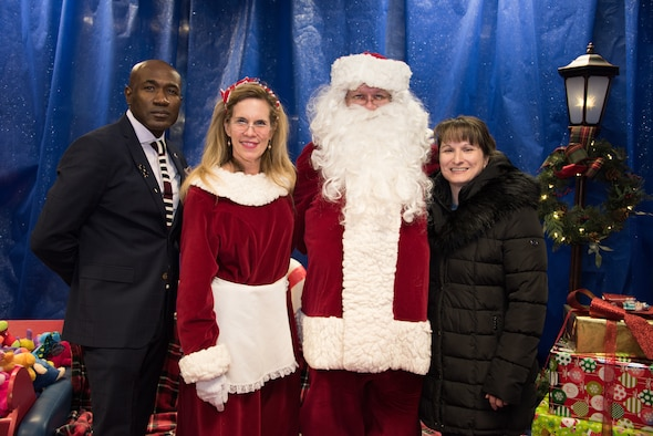 Col. Jennifer Grant, 50th Space Wing commander, and Chief Master Sgt. Boston Alexander, 50th SW command chief, spend time with Mr. and Mrs. Claus at the Annual Children's Holiday Festival Winter Extravaganza at the fitness center at Schriever Air Force Base, Colorado, Dec. 1, 2018. Events like these are designed to meet the 50th SW's priority of taking care of Airmen and their families always. (U.S. Air Force photo by 2nd Lt. Idalí Beltré Acevedo)
