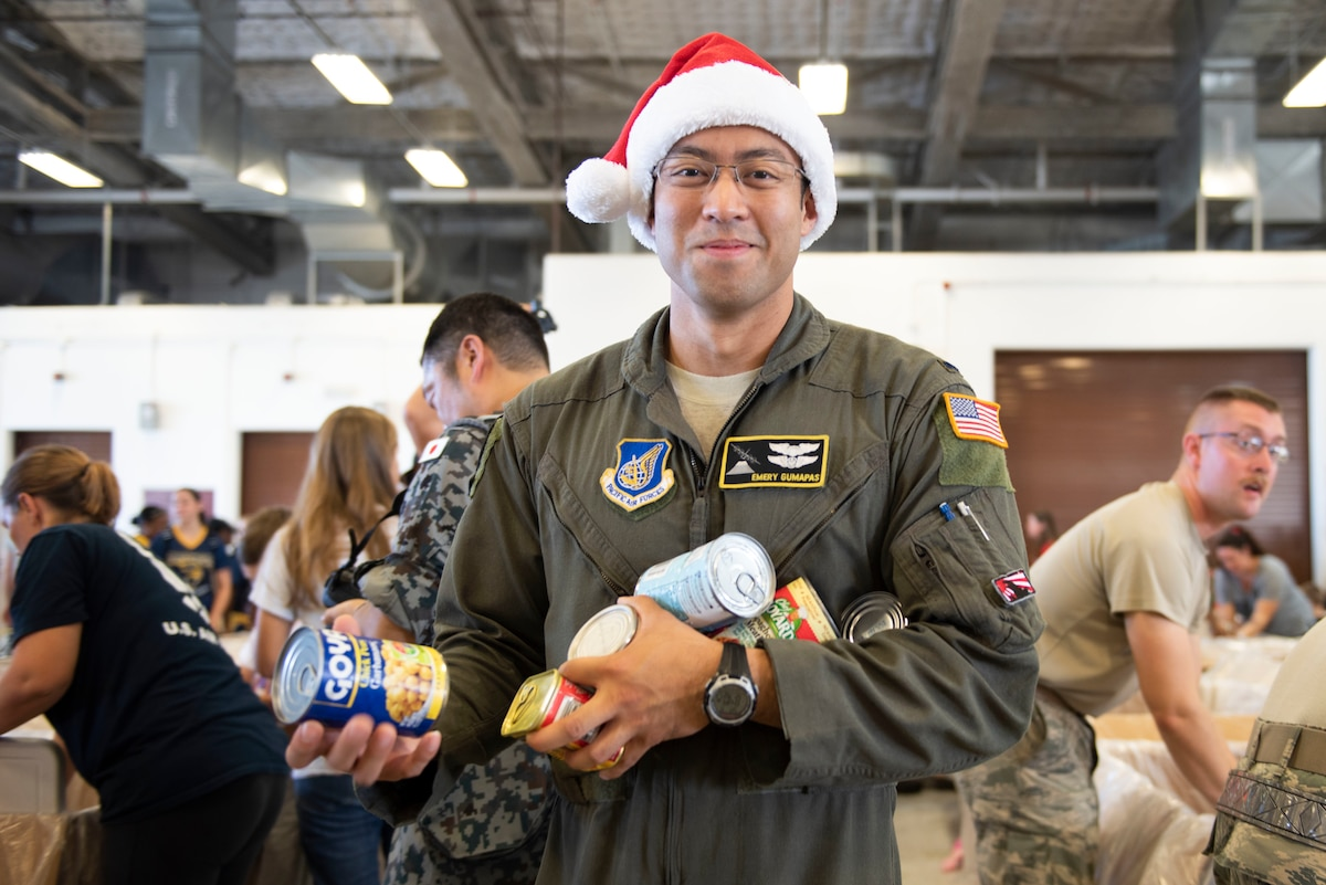 Airman carries canned food to be delivered during Operation Christmas Drop 2018.