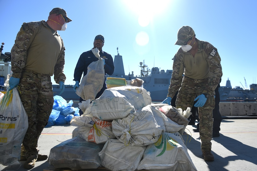 Troops work around sacks on a pier.