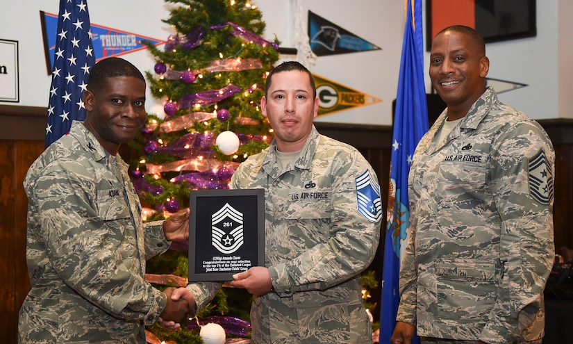 Col. Adam Terrence, 628th Air Base Wing commander, left, and Chief Master Sgt. Michael Cole, 628th Air Base Wing command chief, right, congratulate chief select, Senior Master Sgt. Armando Chavez, 628th Logistics Readiness Squadron, flight superintendent, during a release party held Joint Base Charleston, S.C., Dec. 7, 2018.