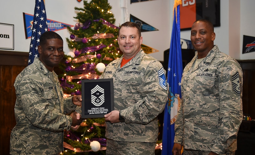 Col. Terrence Adams, 628th Air Base Wing commander, left, and Chief Master Sgt. Michael Cole, 628th Air Base Wing command chief, right, congratulate chief select, Senior Master Sgt.Patrick Hackman, 628th Communications Squadron operations flight superintendent, during a release party held Dec. 7, 2018, at Joint Base Charleston, S.C. A release party was held in their honor at the Charleston Club, where base members gathered in support and celebration.