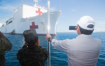 President Juan Orlando Hernandez of Honduras takes a picture as he is transported to the hospital ship USNS Comfort (T-AH 20) for a tour and luncheon.