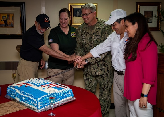 Capt. William Shafley, commander, Task Force 49 (center), President Juan Orlando Hernandez of Honduras (center-right), First Lady Ana Rosalinda Garcia Carias de Hernandez (right), Heide Fulton, Charge d'Affaires at the U.S. embassy in Honduras (center-left) and Sergio de la Pena, U.S. deputy assistant secretary of defense for western hemisphere affairs, cut a cake during a luncheon hosted aboard the hospital ship USNS Comfort (T-AH 20).