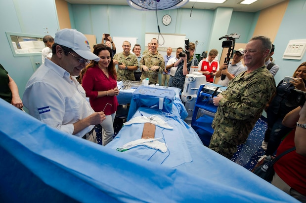 U.S. Navy Capt. Kevin Buckley (right), commanding officer, Medical Treatment Facility, aboard the hospital ship USNS Comfort (T-AH 20), gives a tour of the ship to President Juan Orlando Hernandez of Honduras and First Lady Ana Rosalinda Garcia Carias de Hernandez.