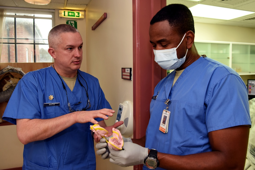 U.S. Air Force Maj. Jeremy Matis, 48th Dental Squadron general dentist, and Tech. Sgt. Andre Andrews, 48th DS dental technician, discuss a patient's dental impressions at the RAF Mildenhall Dental Clinic, RAF Mildenhall, England, Dec. 3, 2018. The 48th DS, which is permanently based at RAF Lakenheath, consists of 108 personnel – dental officers, enlisted technicians, administrators, medical equipment technicians and other essential personnel.  (U.S. Air Force photo by Airman 1st Class Brandon Esau)
