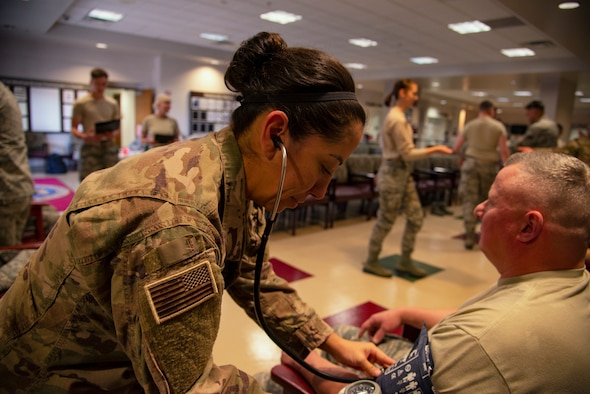 Staff Sgt. Jennifer Lopez, a 302nd Aeromedical Staging Squadron medical technician, takes the blood pressure of a reservist during the Air Force Reserve Command's 302nd Airlift Wing December unit training assembly at Peterson Air Force Base, Colorado, Dec. 2, 2018.