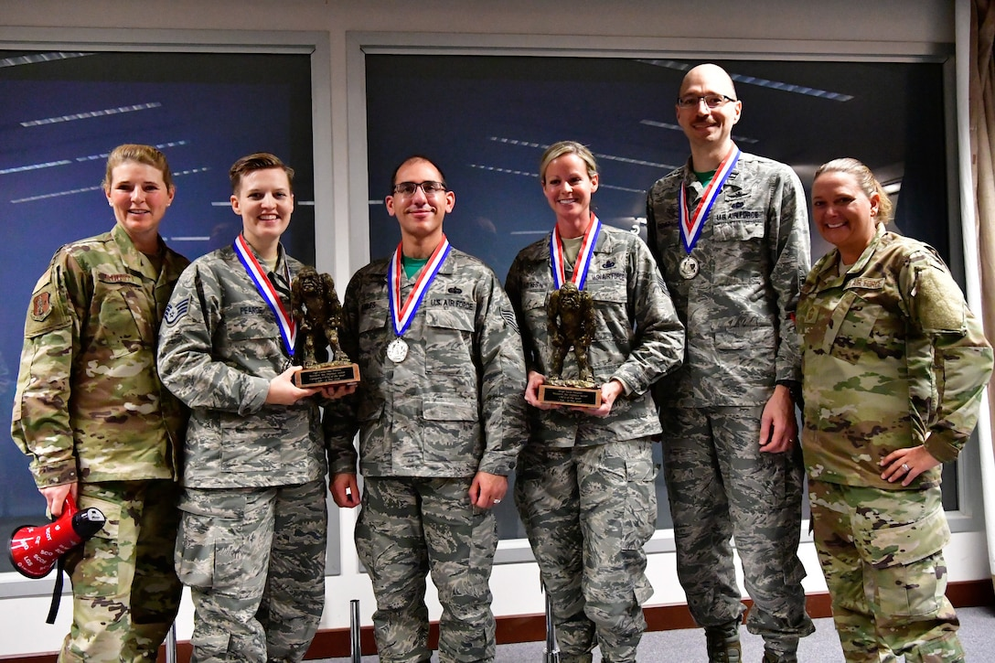 The 225th Support Squdron annual award winners pose with their Bigfoot trophies and medals Dec. 1, 2018 on Joint Base Lewis-McChord, Washington. Pictured from left to right are:  Col. Paige Abbott (left), 225th SS commander;  Category I Drill Status Guardsmen of the Year Staff Sgt. Catherine Pearce, emergency management specialist; NCO of the Year Tech. Sgt. Edwin Aviles, 225th Support Squadron cyber infrastructure technician; SNCO of the Year Master Sgt. Sara Haynes, NCOIC of logistics; CGO of the Year Capt. Paul Fisher, chief of mission system and Chief Master Sgt. Laurie Doyle, 225th SS chief enlisted manager.  Not pictured are: Category I Civilian of the Year Barry Arzberger, HVAC technician; Category II Civilian of the Year Bruce Robie,  National Airspace System Defense program manager (U.S. Air National Guard photo by Maj. Kimberly D. Burke)