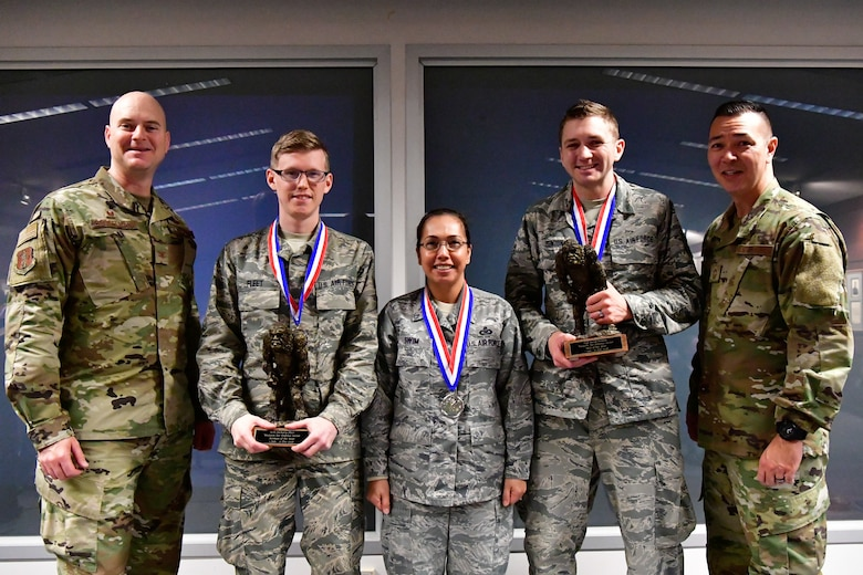 The 225th Air Defense Squadron annual award winners pose with their Bigfoot trophies and medals Dec. 1, 2018 on Joint Base Lewis-McChord, Washington. Pictured from left to right are:  Col. Brett Bosselmann, 225th ADS commander; Airman of the Year Senior Airman Zachary Fleet, interface control technician;  SNCO of the Year Senior Master Sgt. Julietta Swin, superintendent of data link operations; NCO of the Year Staff Sgt. Jared Denton, NCOIC of surveillance training. Not pictured is: CGO of the Year Capt. Marvin Yamada, weapons flight commander.  (U.S. Air National Guard photo by Maj. Kimberly D. Burke)