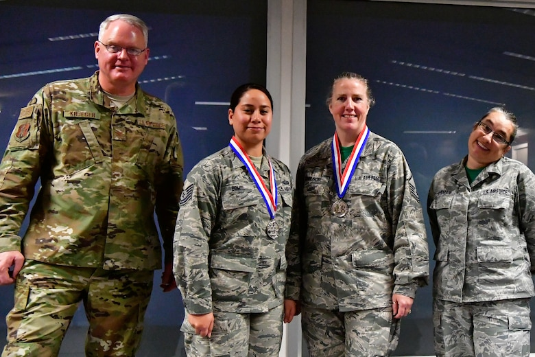 The 225th Air Defense Group command staff annual award winners pose with their Bigfoot trophies and medals Dec. 1, 2018 on Joint Base Lewis-McChord, Washington. Pictured from left to right are:  Col. William Krueger, 225th ADG commander; NCO of the Year Tech. Sgt. Jocelyn Somol, military personalist; SNCO of the Year Master Sgt. Malinda Gonnuscio, training manager; and  Senior Master Sgt. Rebekah St. Romain, 225th ADG superintendent. Not pictured are: Category I Civilian of the Year Richard Gonzales, military personelist; Category II Civilian of the Year Kimberly Burke, public affairs manager; and Drill Status Guardsmen Company Grade Officer Capt. Colette Muller, public affairs officer.  (U.S. Air National Guard photo by Maj. Kimberly D. Burke)