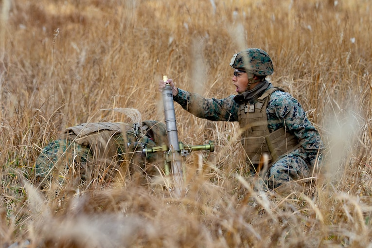 Two Marines prepare to fire a mortar in a field.
