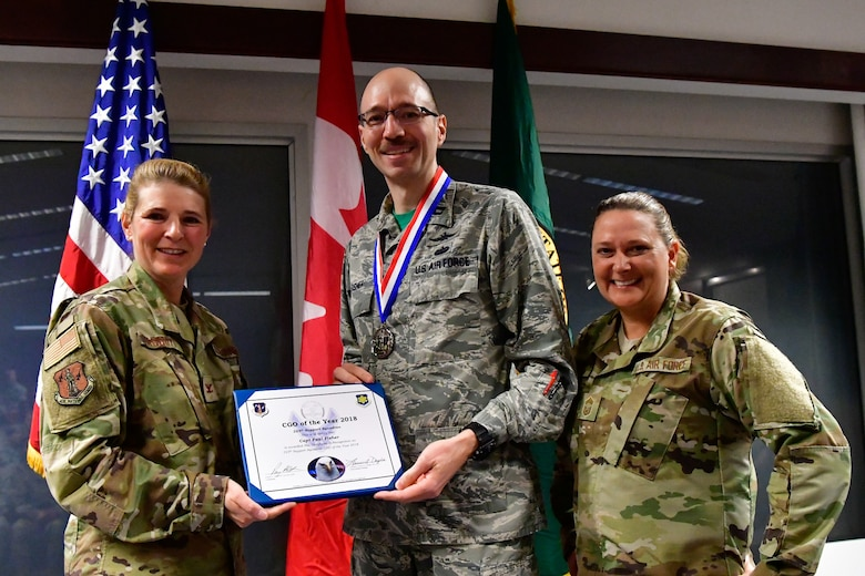 Capt. Paul Fisher, 225th Support Squadron chief of mission system is named the 225th SS Company Grade Officer of the Year Dec. 1, 2018 on Joint Base Lewis-McChord.  Fisher poses with Col. Paige Abbott (left), 225th SS commander and Chief Master Sgt. Laurie Doyle, 225th SS chief enlisted manager. (U.S. Air National Guard photo by Maj. Kimberly D. Burke)