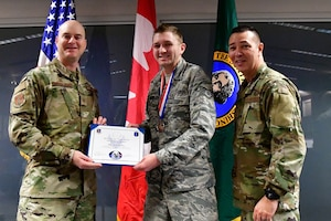 Staff Sgt. Jared Denton, 225th Air Defense Squadron NCOIC of surveillance training is named the 225th ADS NCO of the Year Dec. 1, 2018 on Joint Base Lewis-McChord.  Denton poses with Col. Brett Bosselmann (left), 225th ADS commander and Chief Master Sgt. Allan Lawson, 225th ADS chief enlisted manager. (U.S. Air National Guard photo by Maj. Kimberly D. Burke)