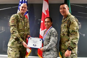 Senior Master Sgt. Julietta Swin, 225th Air Defense Squadron superintendent of data link operations is named the 225th ADS NCO of the Year Dec. 1, 2018 on Joint Base Lewis-McChord.  Swim poses with Col. Brett Bosselmann (left), 225th ADS commander and Chief Master Sgt. Allan Lawson, 225th ADS chief enlisted manager. (U.S. Air National Guard photo by Maj. Kimberly D. Burke)
