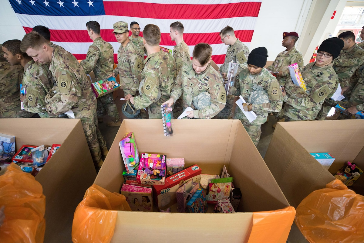 Soldiers drop toys into large cardboard boxes.