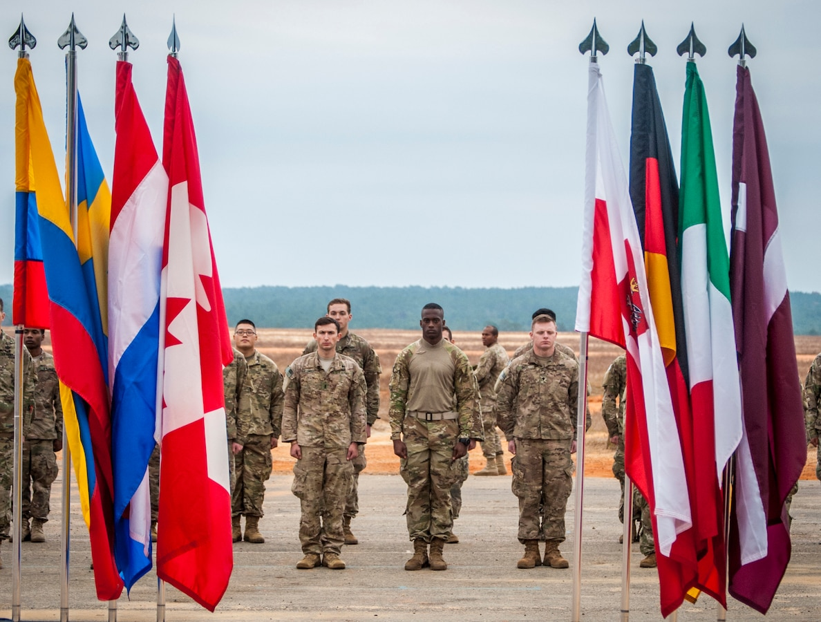 Soldiers stand in formation behind multinational flags.