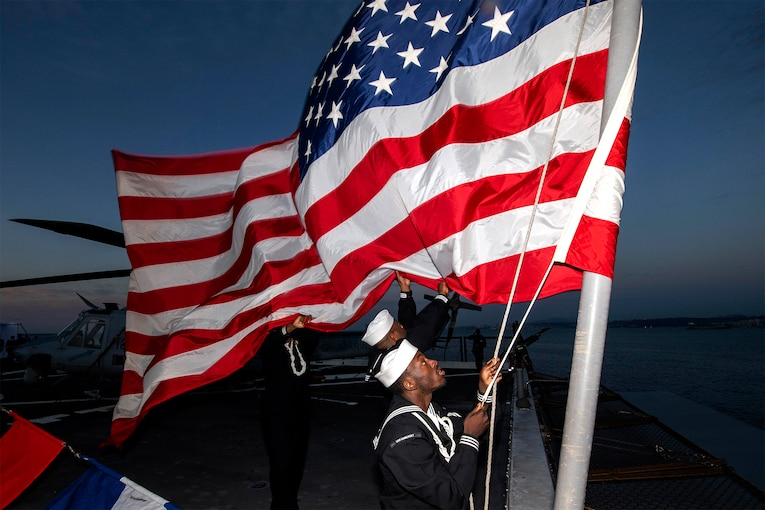 A sailor raises the American flag during a burial-at-sea ceremony.