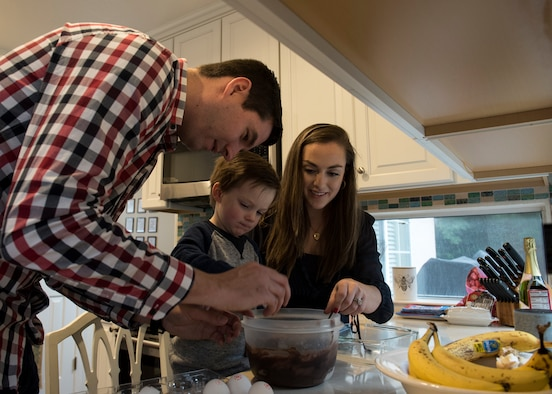 Capt. Steven Noller, 21st Airlift Squadron pilot, his spouse Morgan and their son Camden, prep a cake for baking in their home in Vacaville, California, Dec. 7, 2018. Morgan won the 2018 Joan Orr Air Force Spouse of the Year Award. (U.S. Air Force photo by Lan Kim)