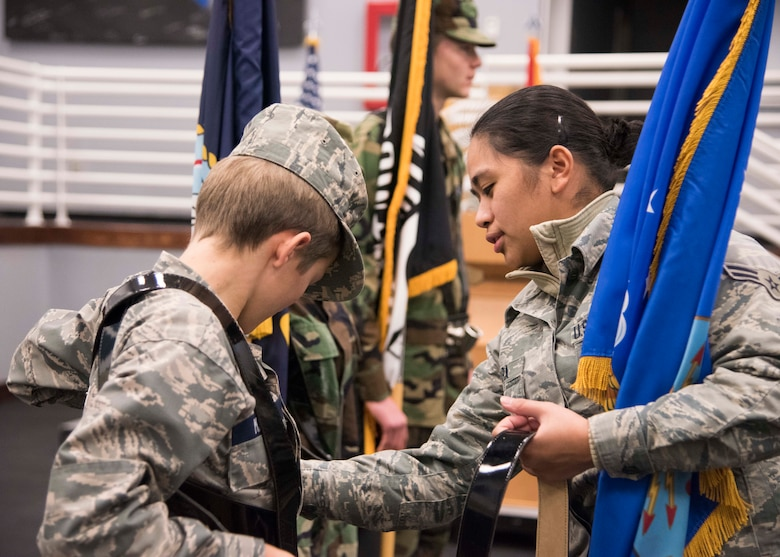 "Christian Maple, Civil Air Patrol Spokane Composite Squadron cadet, receives assistance from Airman 1st Class Larrah Lara, 92nd Air Refueling Wing Honor Guardsmen, while practicing ""presenting colors"" at Fairchild Air Force Base, Washington, Nov. 26, 2018. Fairchild Honor Guard teams are composed of Airmen from different career fields, bringing a diversity of age and experience. (U.S. Air Force photo/ Senior Airman Ryan Lackey)"