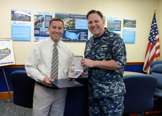 Brian Caine, TUBA Technical Program Manager, receives the Navy Meritorious Civilian Service Award on Nov. 7, 2018, from Naval Surface Warfare Center, Carderock Division Commanding Officer Capt. Mark Vandroff for his contributions in the area of acoustics systems for undersea warfare. (U.S. Navy photo by Devin Pisner/Released)
