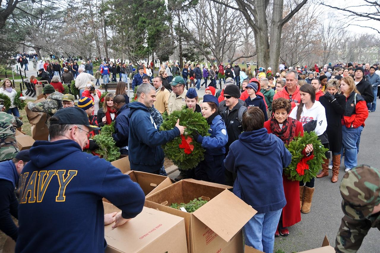 Navy sailors distribute wreaths to volunteers.