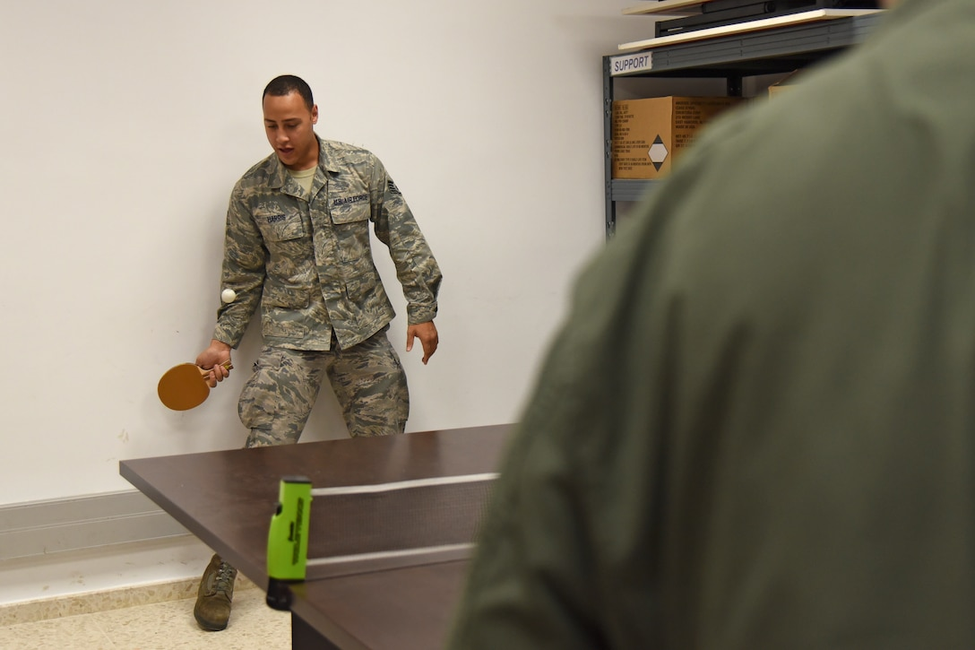 Staff Sgt. Edward Harris, 92nd Aircraft Maintenance Squadron crew chief, plays table tennis with Col. Derek Salmi, 92nd Air Refueling Wing commander, during a site visit Dec. 4, 2018, at Morón Air Base, Spain. During the month of December, more than 40 holiday care packages made their way to Team Fairchild Airmen stationed at Morón AB as part of KREM 2 News' initiative, Treats 2 Troops. (U.S. Air Force photo/Staff Sgt. Mackenzie Mendez)