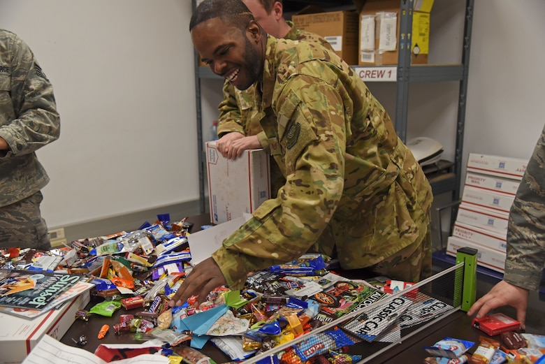 Tech. Sgt. Jonathan Rogers, 93 Air Refueling Squadron boom operator, opens a Treats 2 Troops care package Dec. 4, 2018, at Morón Air Base, Spain. For over a month leading up to the annual Treats 2 Troops packing event at Fairchild Air Force Base, Washington, thousands of items are collected from the Inland Northwest Community including candy, snacks, lip balm, office supplies and toiletries. Local schools in the area also contribute to the creation of care packages by making handmade holiday cards. (U.S. Air Force photo/Staff Sgt. Mackenzie Mendez)