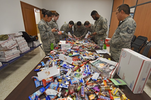 Team Fairchild Airmen stationed abroad open a Treats 2 Troops package Dec. 4, 2018, at Morón Air Base, Spain. Treats 2 Troops is part of KREM 2 News' initiative to spread holiday cheer to military service members stationed abroad during the holiday season. (U.S. Air Force photo/Staff Sgt. Mackenzie Mendez)